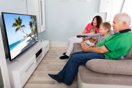 Grandparents And Kids Watching Television On Couch Together At Home Archivio Fotografico