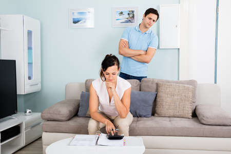 suspicious: Suspicious Man Looking At His Wife Busy Calculating Bills On Sofa At Living Room Stock Photo