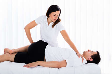 Young Female Therapist Massaging Relaxed Mans Leg In Spa Stock Photo