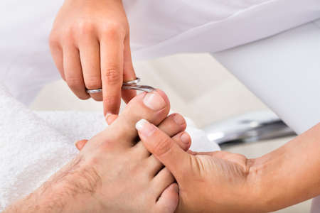 toenail: Close-up Of A Manicurist With Scissors Trimming Persons Toenail