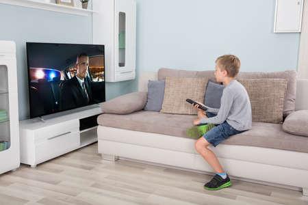 Kid con mando a distancia sentado en el sofá viendo la película en tv Foto de archivo - 65319909