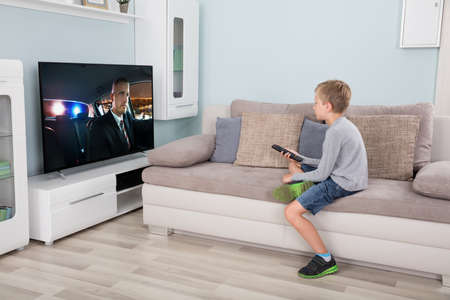 Kid with remote control sitting on couch watching movie on tv Imagens