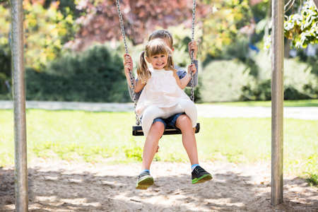 niños sentados: Two Happy Children - Brother And Sister Enjoying Swing  In The Park Foto de archivo