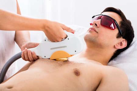 Terapista che dà Trattamento laser Epilazione a Young Man In Spa Archivio Fotografico