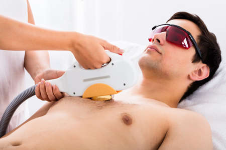 shirtless man: Therapist Giving Laser Epilation Treatment To Young Man In Spa Stock Photo