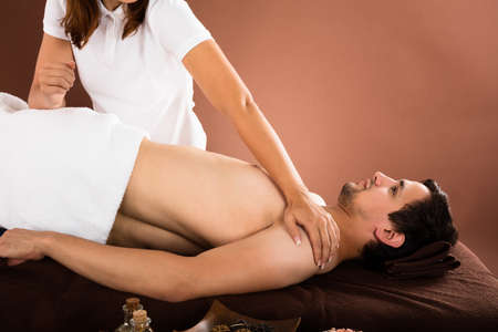 female therapist: Young Man Receiving Massage Treatment From Female Therapist In Spa