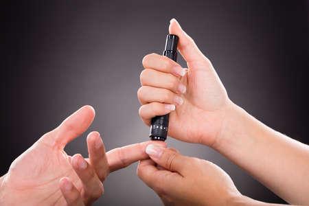 pacjent: Close-up lekarza sprawdzanie poziomu cukru Pacjenta Z Glukometr