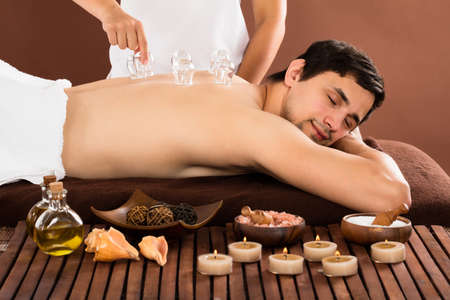 Persons Hand Giving Cupping Treatment To Relaxed Young Man Stockfoto