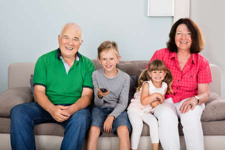multi age: Multi Generations Family With Two Kids Watching Movie On TV Sitting On Couch Together Stock Photo