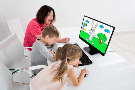 Happy Kids Using Painting Application On Desktop Computer Together With Grandparents