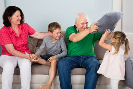 family fight: Older Happy Grandparents Having Pillow Fight With Kids On Couch Together At Home Stock Photo