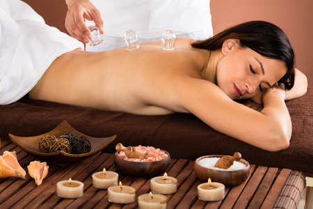 Happy Young Woman Receiving Cupping Treatment On Back In Spa