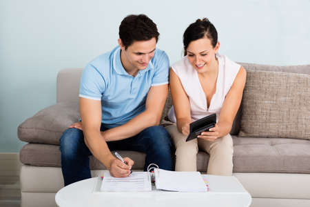 calculating: Young Happy Couple Sitting On Sofa Calculating Budget At Home