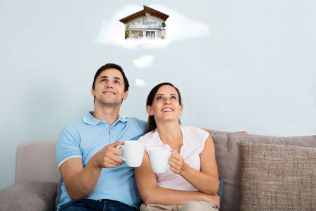 man sit: Happy Couple Dreaming Of Having Future Home While Sitting On Sofa