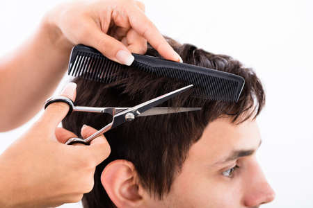man haircut: Happy Young Man Getting Haircut From Hairdresser