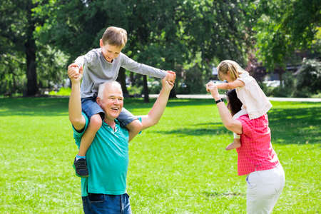 multi age: Happy Family Having Fun Doing Piggyback Ride With Kids In Park