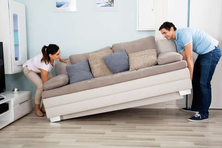 placing: Young Happy Couple Placing Sofa Together In Living Room At Home Stock Photo