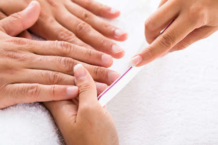 Close-up Of A Manicurist Filing Persons Nails In Salon