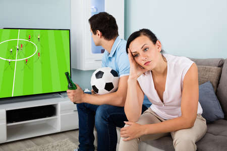 Sad Woman Sitting Beside A Man Busy Watching Sports On Television At Home photo