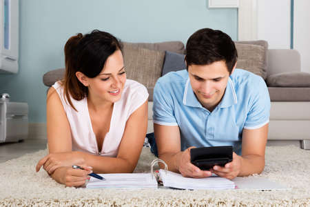 saving: Happy Couple Lying On Carpet Calculating Bills Together At Home