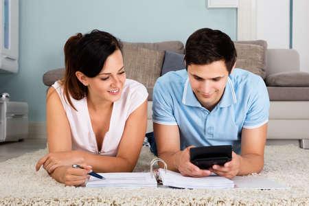 ahorros: Pareja feliz en la alfombra Cuentas calculadoras junto en el país