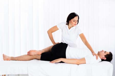 スパでリラックスした男の足をマッサージの若い女性セラピスト