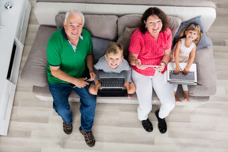 women sitting: Family With Kids Using Laptop Computers And Tablets On Couch At Home