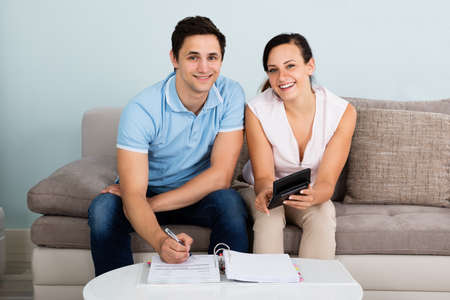Young Happy Couple Sitting On Sofa Calculating Budget At Home