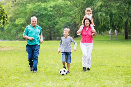 family playing: Happy Family Playing Soccer Game With Grandchildren Together In Park. Running For Ball