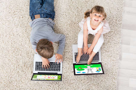 laptop computers: Two Kids With Laptop Computers On Carpet At Home