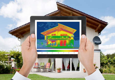 heat loss: Close-up Of The Person Detecting Heat Loss Outside The House Using Digital Tablet