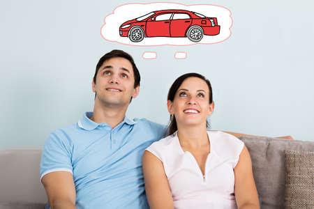 soñando: Joven pareja feliz Sueño con tener coche mientras está sentado en el sofá