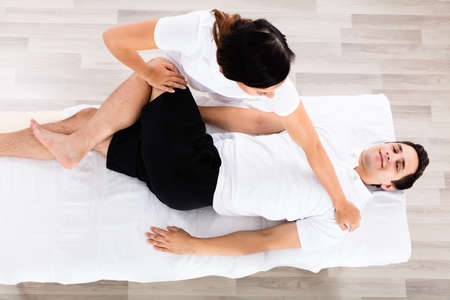 High Angle View Of A Young Female Therapist Massaging Relaxed Mans Leg