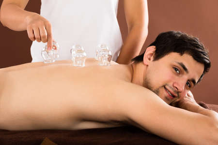 Relaxed Young Man Receiving Cupping Treatment On Back In Spa Stock Photo