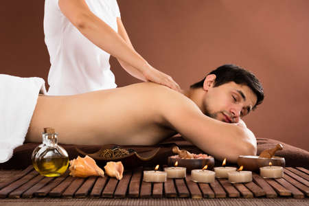 two men: Young Man Receiving Shoulder Massage From Therapist In Spa