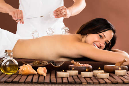 Therapist Giving Cupping Treatment To Young Woman In Beauty Spa