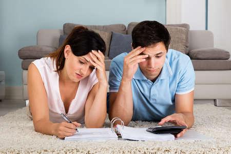 persona triste: Pareja joven infeliz Cuentas calculadoras mientras está acostado en la alfombra en casa