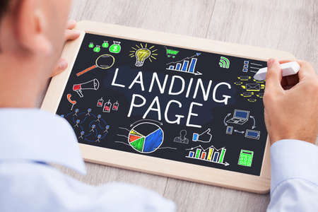 high angle view: High Angle View Of Businessperson Drawing Landing Page Concept On Slate At Wooden Desk