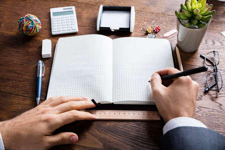 diaries: High Angle View Of Businessperson Holding Pen On Blank Diary At Wooden Desk