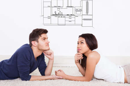 Young Couple Lying On Carpet Thinking Of Having Modern Kitchen In Their House