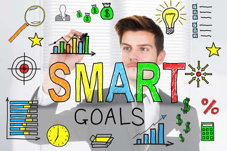 smart goals: Successful Businessman Drawing Smart Goals Concept On Transparent Glass In Office