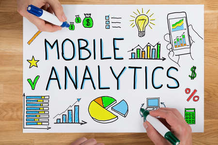 elevated: Close-up Of Two Businesspeople Drawing Mobile Analytic Concept On Paper Using Colorful Marker On Wooden Desk Stock Photo