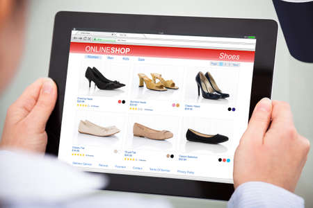 web shop: Close-up Of Person Purchasing Footwear While Doing Online Shopping On Digital Tablet Stock Photo