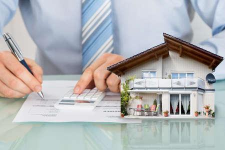 사업가 계산기와 하우스 모델에 사무실 책상을 사용하여 넓은 구역을 계산