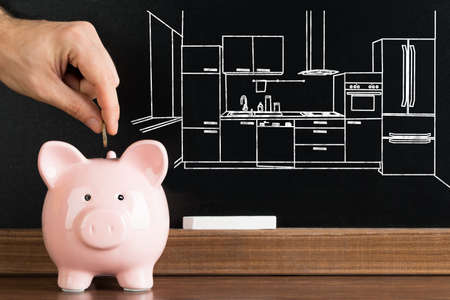 inserting: Close-up Of Person Inserting Coin In Piggybank With Kitchen Image Drawn On Blackboard In The Background