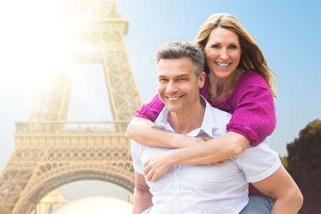 Retrato de hombre feliz a cuestas a su esposa cerca de la Torre Eiffel Foto de archivo