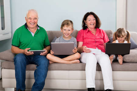 laptop computers: Family Sitting On Couch With Their Laptop Computers And Tablets At Home