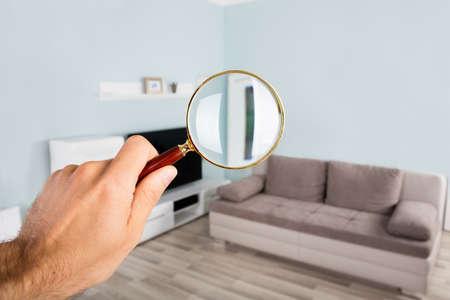 집안에서 돋보기를 사용하여 거실을 확인하는 사람 손의 근접 촬영