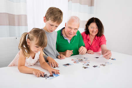 Family Holding Jigsaw Puzzle Pieces While Playing Game Together With Kids Stock Photo - 66552606