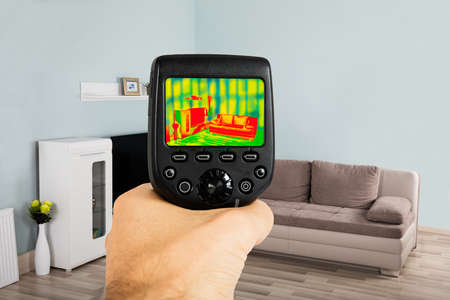 Close-up Of Person Hand Using Infrared Thermal Camera In Living Room At Home Stock Photo